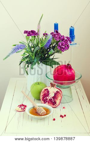 Honey apple pomegranate and flowers on wooden white table