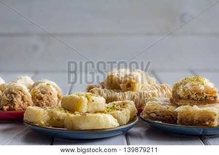 Variety of Baklava on Plates Horizontal on Wooden Table with Copy Space Selective Focus