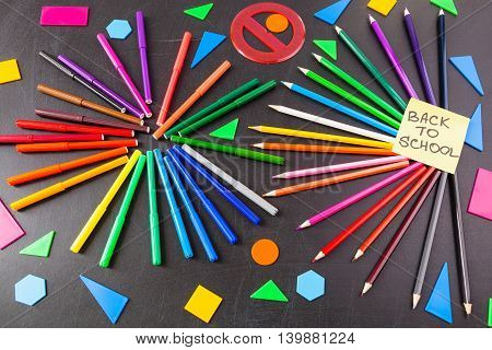 Back to school background with a lot of colorful felt-tip pens and colorful pencils in circles and title