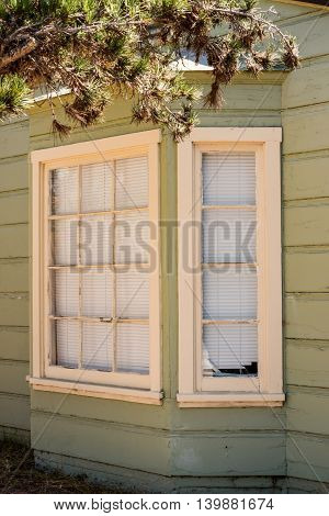 rotten bay window and pale green old wooden house