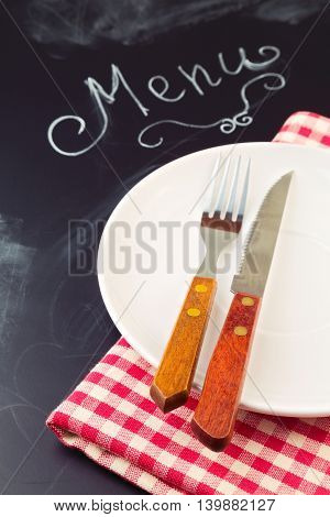 Plate knife and fork on tablecloth over blackboard background with word menu