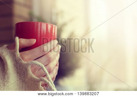 Retro background with red cup in his hands in the comfort of your home / holiday after winter walks
