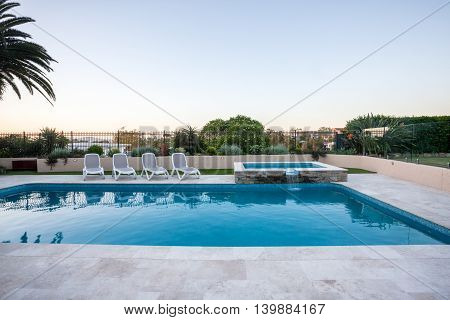 Luxury Swimming Pool With A Small Fountain Covered With Fence