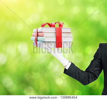 Businessman hand holding stack of colorful book tied up with a ribbon on green background. 3D Rendering