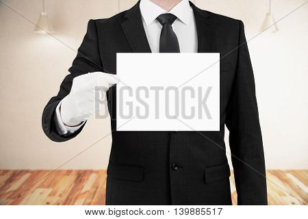 Business man holding blank card on empty room interior background. Mock up