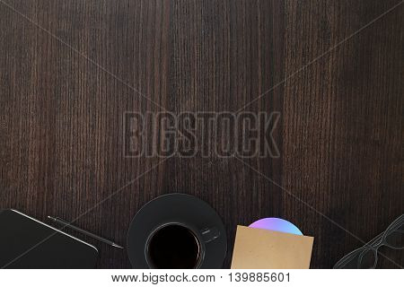 Top view of wooden office desktop with coffee cup cd pen smartphone and glasses. Mock up 3D Rendering