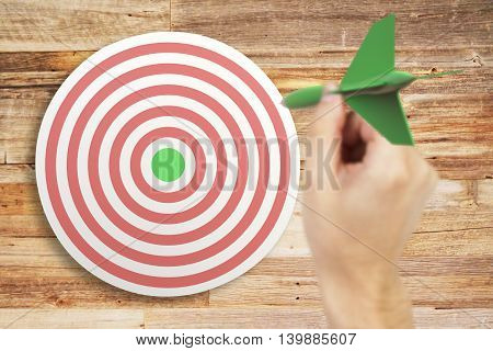 Targeting concept with businessman hand playing darts on aged wooden background. 3D Rendering