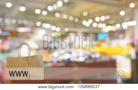 reusable paper shopping bag against blur bokeh of store background online shopping concept