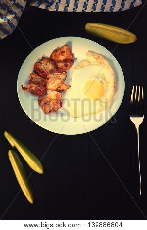 Fried eggs with bacon and fork on a black table