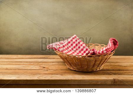 Empty basket with checked tablecloth on wooden table over grunge background