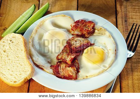 Fried eggs with bacon, bread and fork