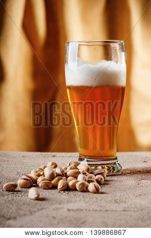 Glass of beer and pistachio nuts on a gray surface
