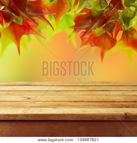 Autumn background with empty wooden deck table and autumn colorful leaves