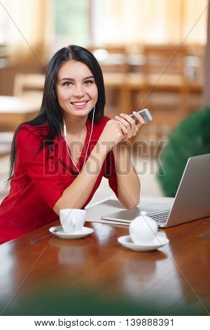 Young businesswoman using phone in coffee shop. Successful businesswoman. Young woman with phone and laptop sitting in cafe looking at the camera.