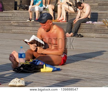 MOSCOW. RUSSIA - July 17, 2016: Heat in Moscow. Sunbathing mid adult man reading a book sitting on the wooden flooring. Dry fountain at the Crimean waterfront. July 17, 2016 in Moscow. Russia