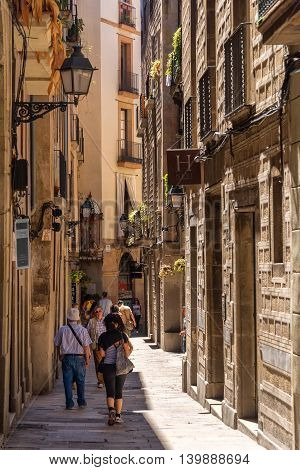 Barcelona Spain - June 19 2016: Pedestrians walk along one of many narrow alleyways that meander throughout the city Barcelona Spain.