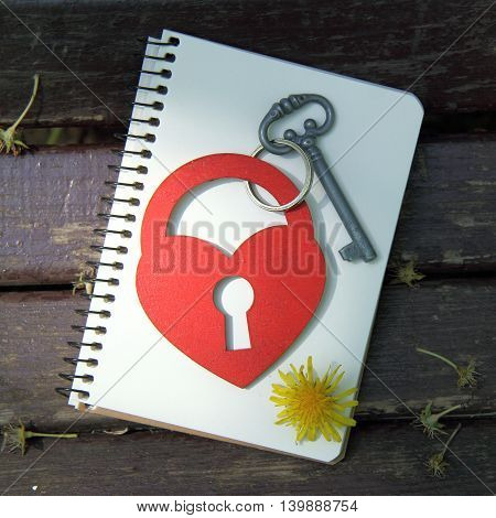 lock key symbol and heart on a notebook with a pencil top view / unusual love letter