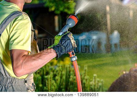 Summer Garden Watering. Caucasian Male Gardener Watering His Beautiful Garden.