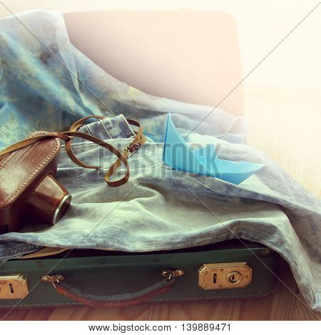 retro background old suitcase with a camera and a paper boat / weekend travel time