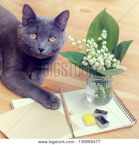 paint brush and a bouquet of lilies of the valley on a background of a cat / cat in still life
