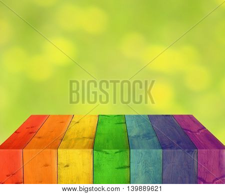 table from multicolored wooden boards with blurred light background