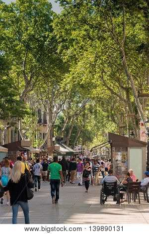 Barcelona Spain -June 19 2016: People fill the tree lined pedestrian mall in Barcelona named Las Ramblas. It's 1.2 kilometers long and filled with stores restaurants and theaters for tourists to see.