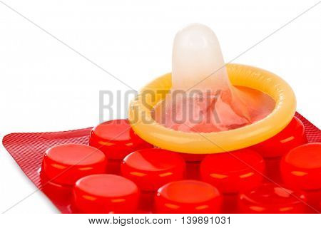 Condom and pills isolated on white backgrounda