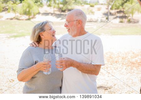 Happy Healthy Senior Couple with Water Bottles Outdoors.