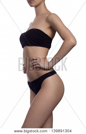 Slim body of the suntanned woman isolated on a white background. Black underwear. Healthy lifestyle Diets.