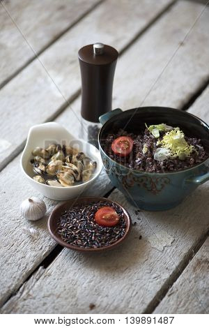 Mussels and black rice, pepper, garlic on a wooden background