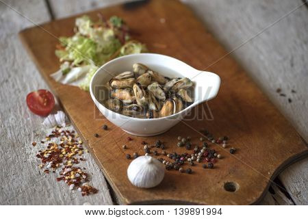Mussels, garlic, pepper, tomato on wooden background