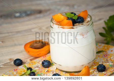 Homemade yogurt with granola blueberries and apricots. Selective focus.