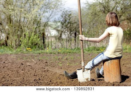 gardener with long shovel in his hand resting on a tree stump in the background digging up the garden / gardener resting after a hard day's work