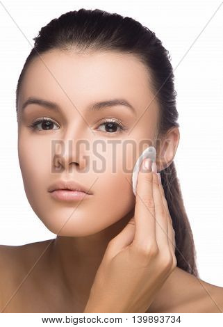 Happy european woman with cotton pad isolated on white background. Beauty fresh girl cleaning face with cotton swab. Beautiful young woman cleaning her face