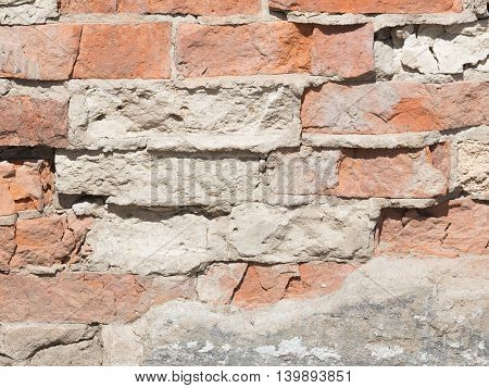 uneven surface of old wall with old chipped bricks held together by a rough gray cement acting