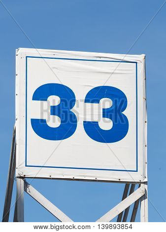 bright sinnee number thirty-three painted on a white kvadoratnom poster with a thin blue border on a background of blue sky