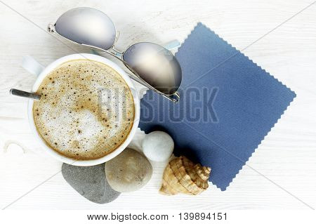 flat lay frothy coffee with sunglasses sea stones and shells / good impression from vacation with a cup of coffee