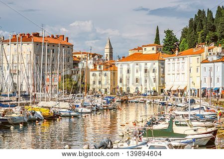 Piran, Slovenia - May 7, 2016: Piran old town center with church tower and marina. Piran is one of Slovenia's major tourist attractions.