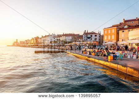 Piran, Slovenia - May 7, 2016: Sunset view on the coastline in Piran town with people sit at the cafe. Piran is one of Slovenia's major tourist attractions.