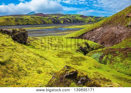 Canyon Pakgil in Iceland. Basalt hills covered with green grass and moss. Streams from melting glaciers flowing down the canyon