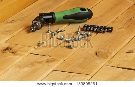 Mechanical screwdriver to tighten the screws on a wooden surface