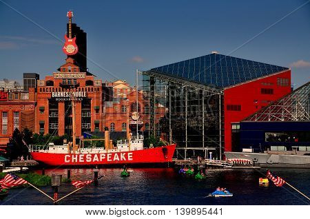 Baltimore Maryland - July 22 2013: Lightship Chesapeake moored in front of the Power Plant commercial complex next to the ultra-modern National Aquarium