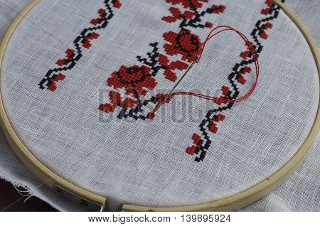 Traditional folk handmade cross-stitch floral pattern in the wooden hoop on the table