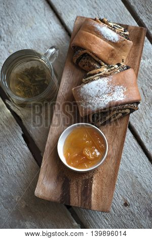 Sweet rolls baked on a wooden stand, jam and green tea in a transparent Cup