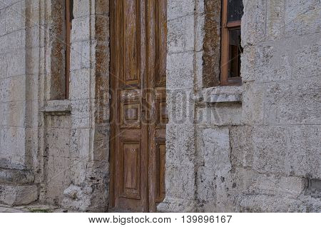 brown old front door into the ruined stone building with broken windows