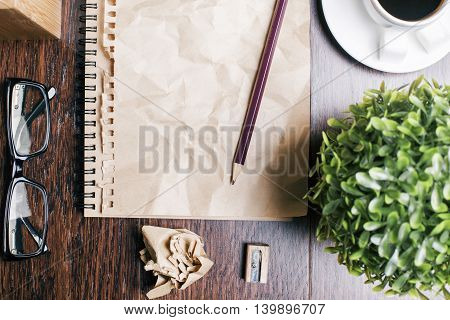 Closeup of spiral notepad with crumpled brown page glasses coffee cup plant sharpener and pencil on wooden table. Top view
