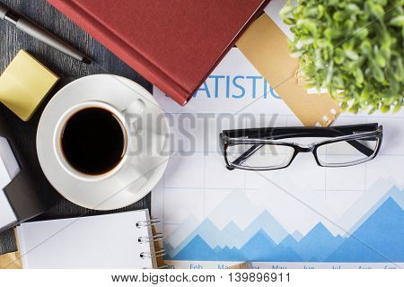 Closeup and top view of coffee cup business report glasses closed hardcover book and stationery items on dark wooden office desktop