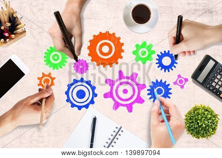 Team work concept with hands drawing abstract colorful cogwheels on wooden office desktop with blank smartphone coffee cup stationery items calculator and decorative plant