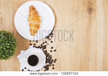Top view of wooden desktop with coffee cup seeds plant croissant on plate and copy space