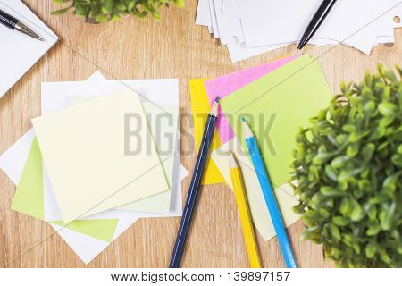 Top view of wooden office desktop with blank colorful ctickers pencils pen and plants. Mock up